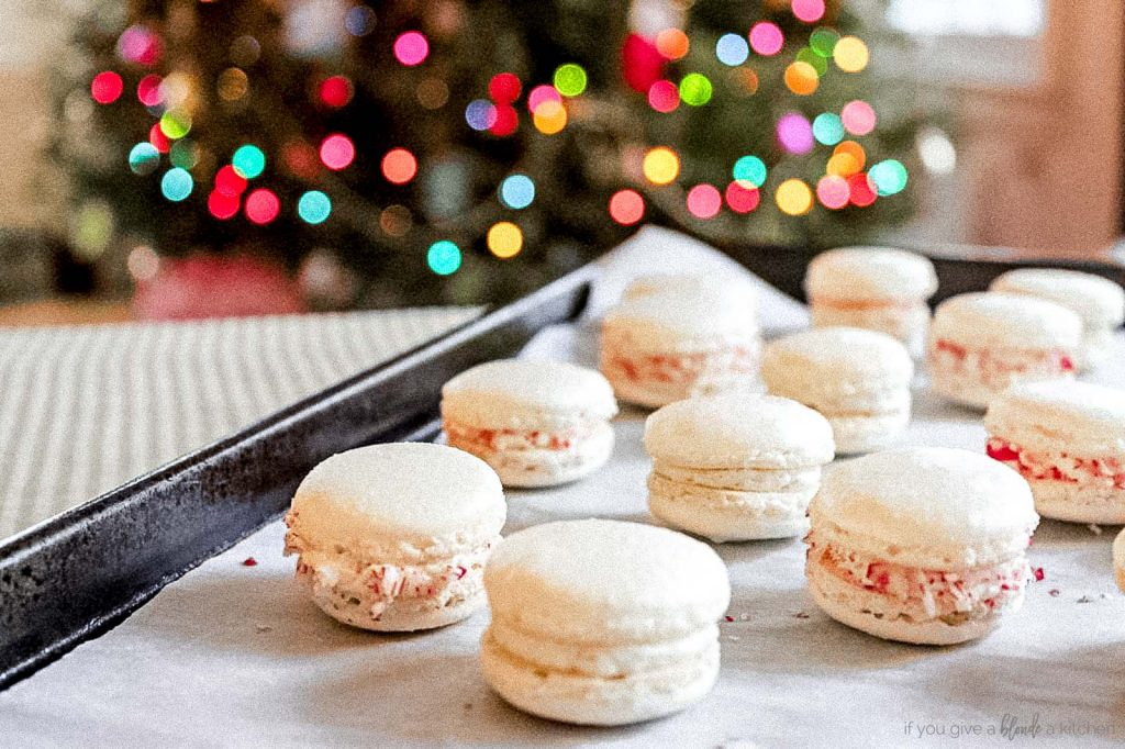 christmas macarons on baking sheet with christmas lights on tree