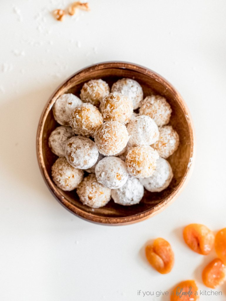 coconut apricot balls in wooden bowl on white surface