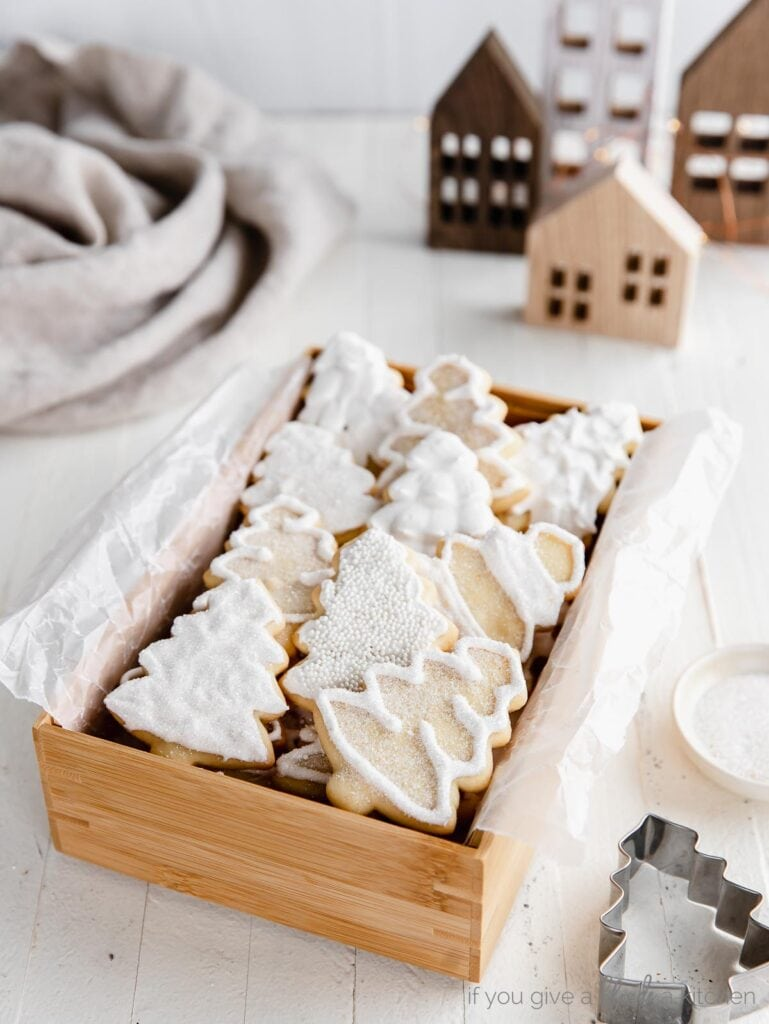 iced christmas tree sugar cookies in a wooden box. brown wooden houses behind box