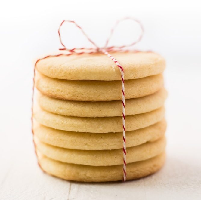 stack of round cut out sugar cookies tied in red baker's twine