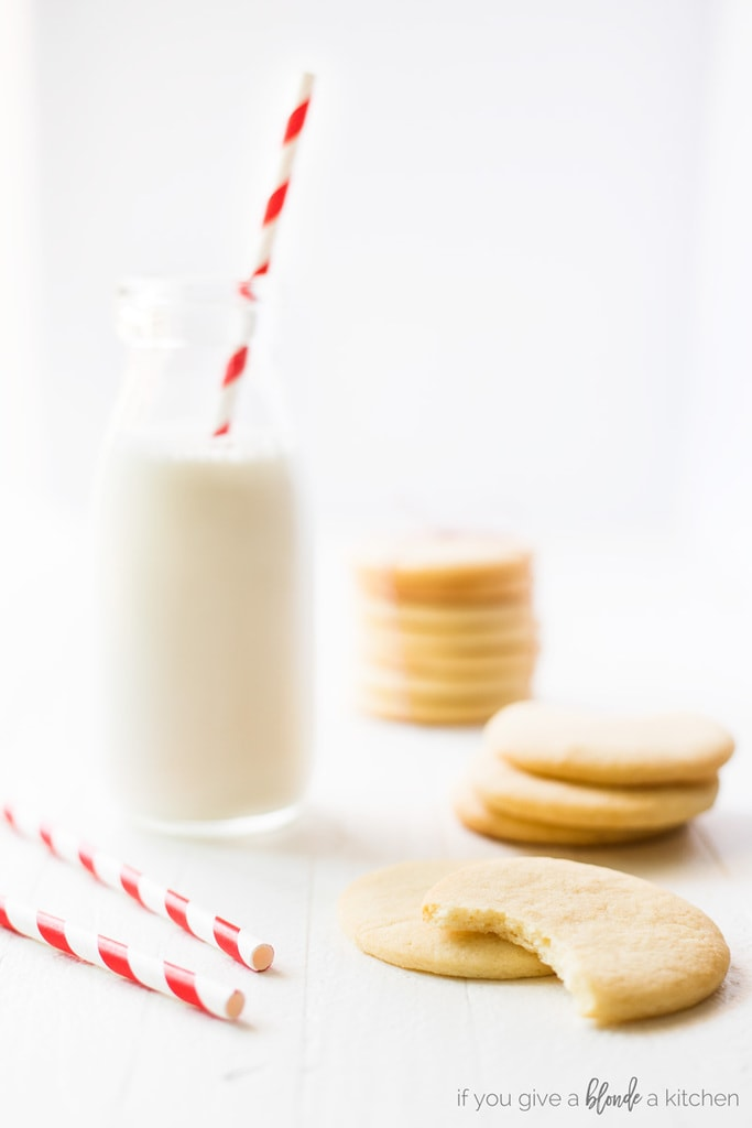 round cut out sugar cookies, one with bite, next to red striped straw, milk bottle nearby