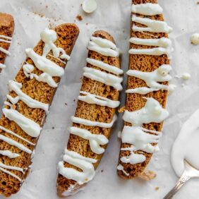 gingerbread biscotti drizzled in white chocolate on top of parchment paper with spoon of melted white chocolate