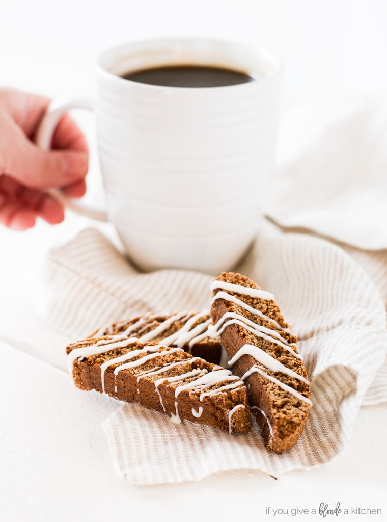 Gingerbread biscotti with white chocolate drizzle and hand reaching for morning coffee