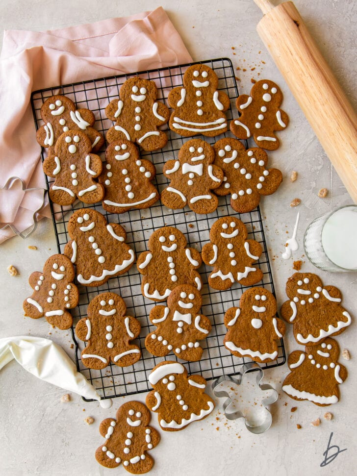 gingerbread man cookies with royal icing on wire cooling rack next to rolling pin and pink kitchen cloth