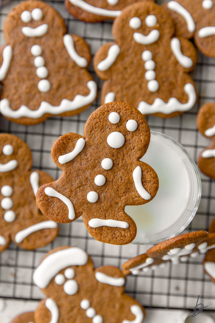 gingerbread man cookie balancing on glass on milk with more cookies around glass