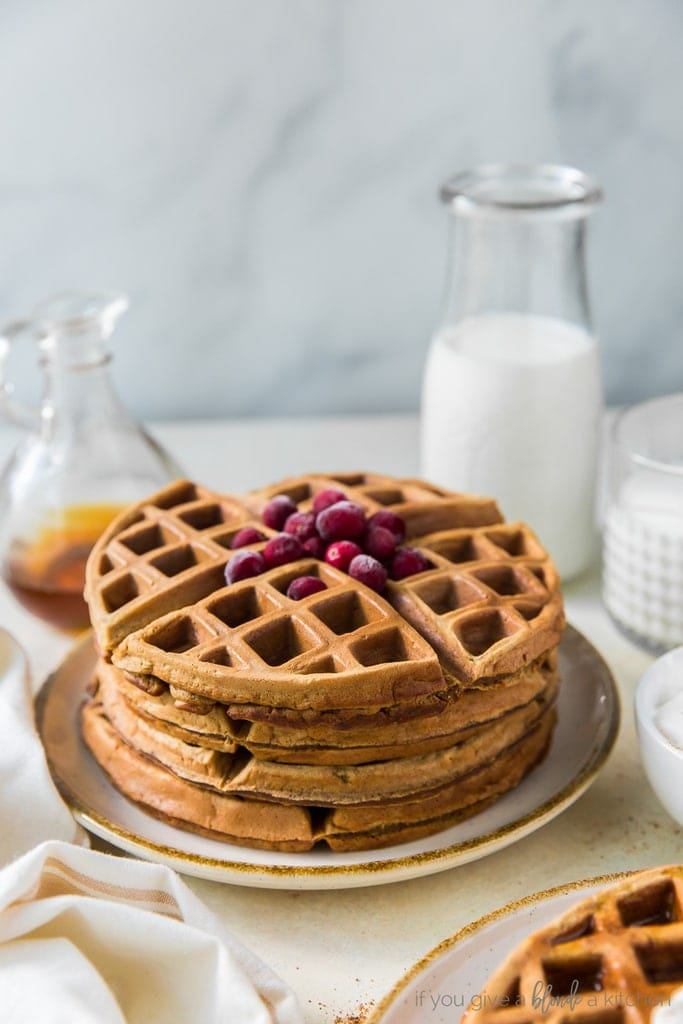 stack of gingerbread waffles topped with sugared cranberries; bottle of milk behind waffles