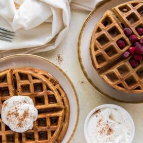 tablescape with gingerbread waffles, eggnog whipped cream, cinnamon and maple syrup