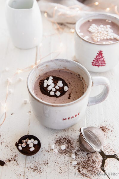 mug of hot chocolate with an open chocolate bomb with mini marshmallows in the mug