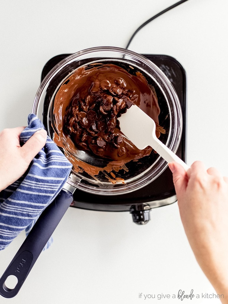 hand holding spatula stirring melted chocolate chips in glass bowl