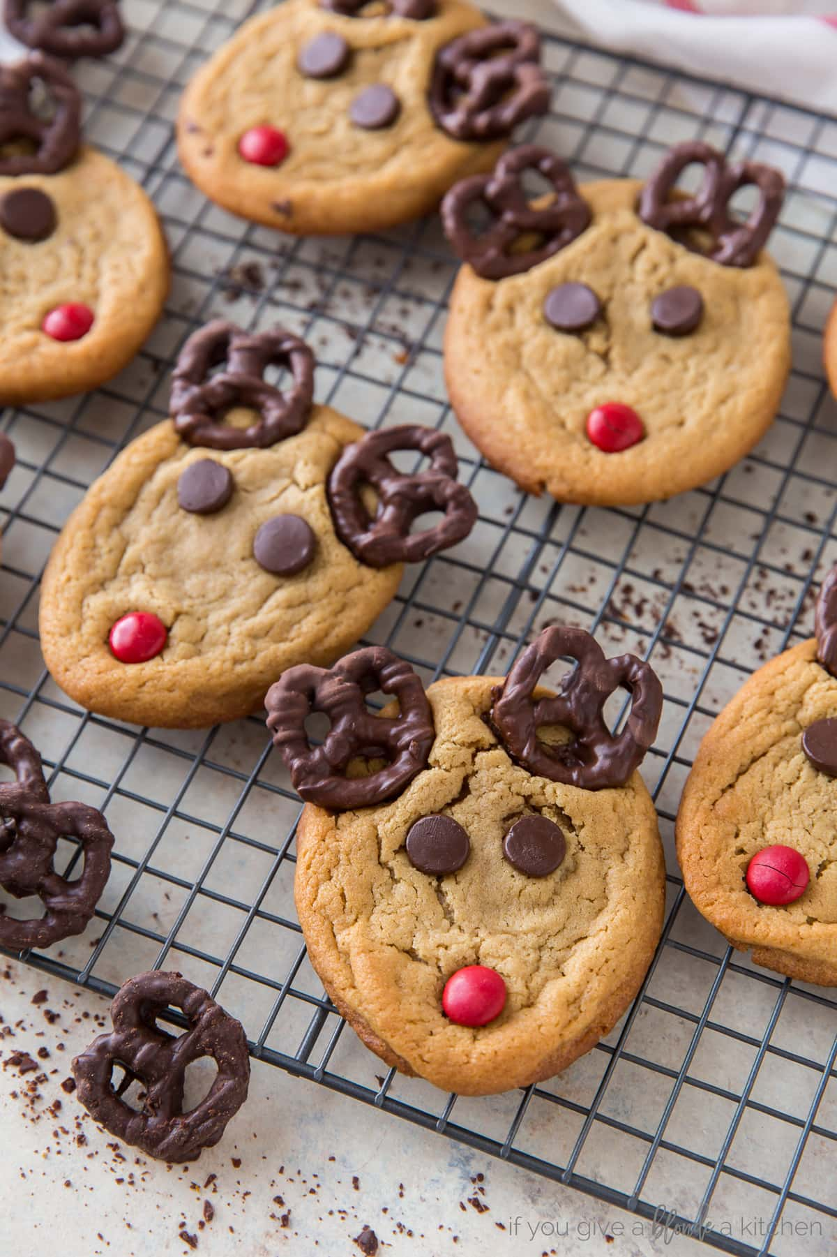 peanut butter reindeer cookies with pretzel antlers on wire cooling rack