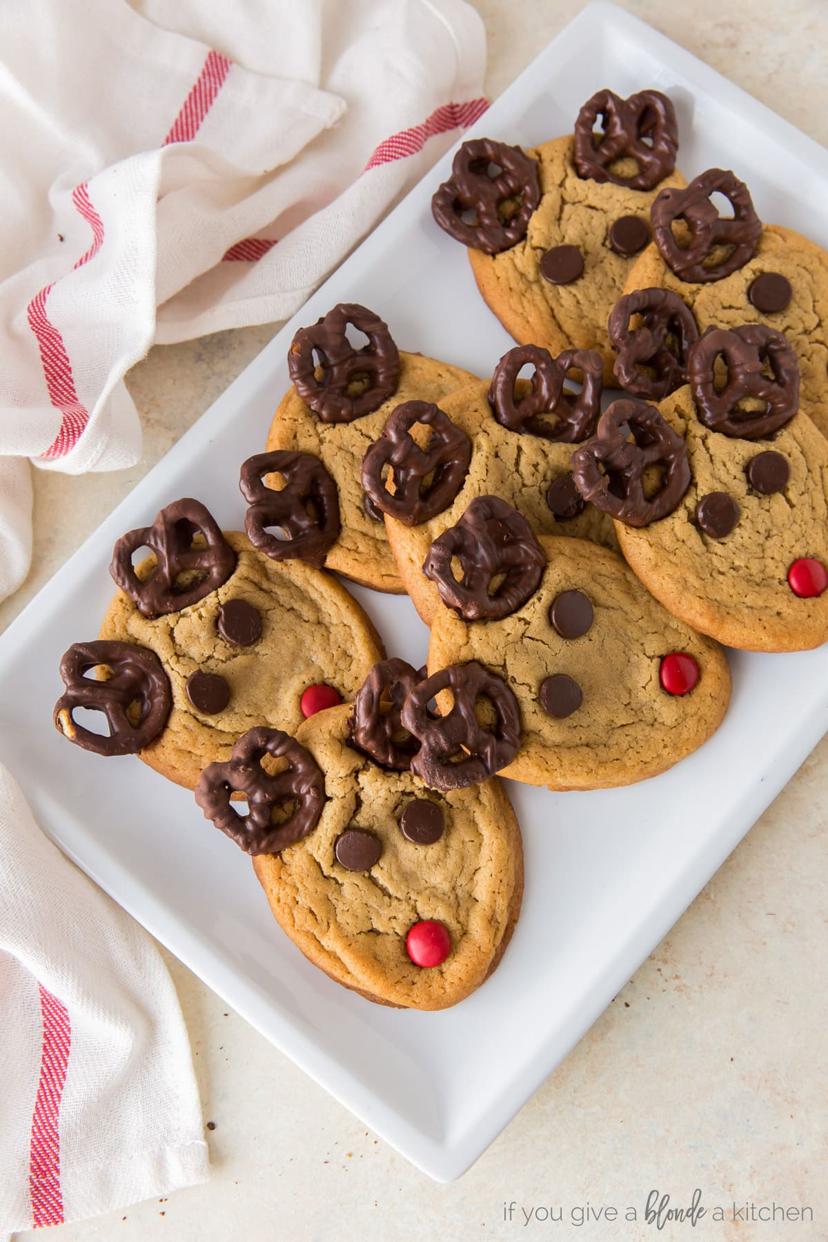 peanut butter reindeer cookies with pretzel antlers, chocolate chip eyes, and red m&m nose