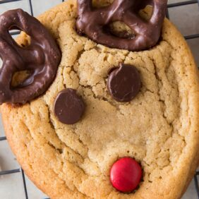 reindeer cookies with chocolate chip eyes, red candy nose and pretzel antlers