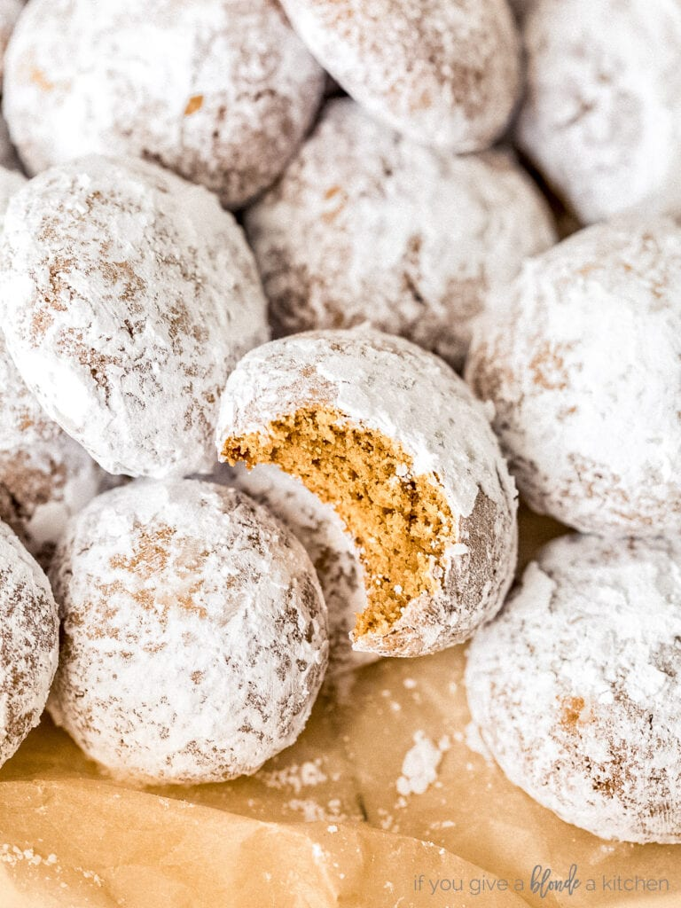 pile of pfeffernusse cookies coated in confectioners' sugar. One cookie with bite