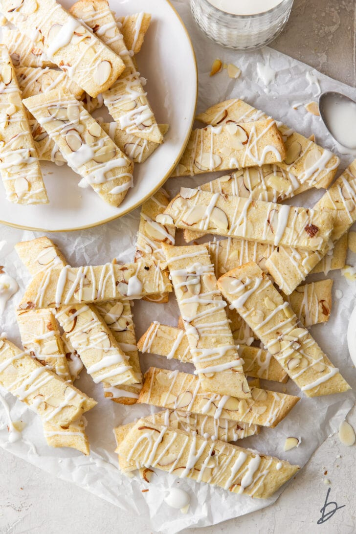 scandinavian almond bars topped with drizzle and slivered almonds in a pile on crinkled parchment paper