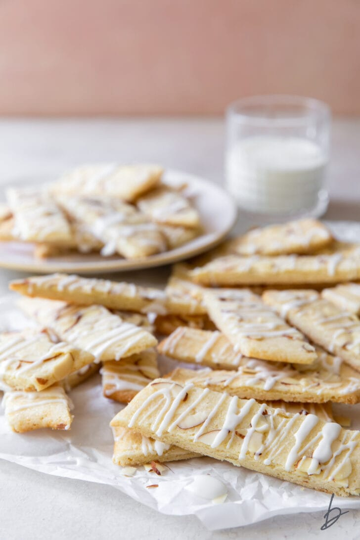 scandinavian almond bars in a pile in front of plate of more bars and glass of milk