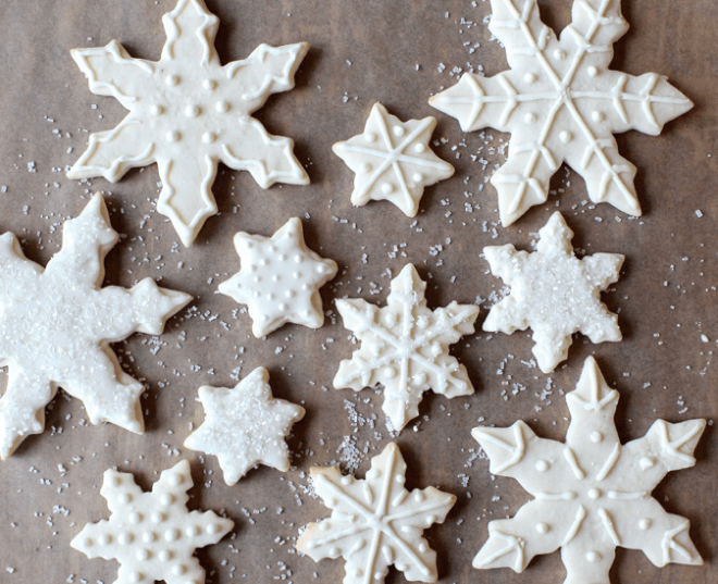 Snowflake sugar cookies decorated with icing and white sprinkles