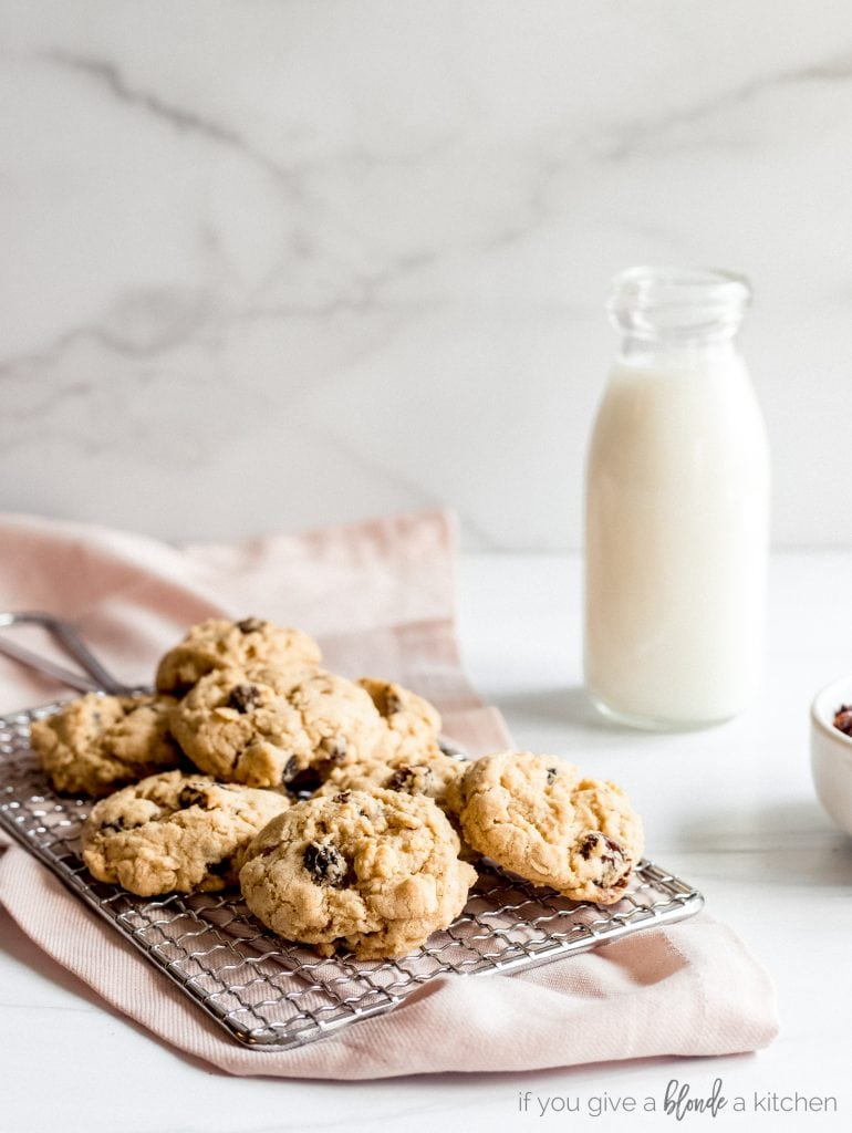 chewy oatmeal raisin cookies, pink kitchen cloth, glass milk bottle