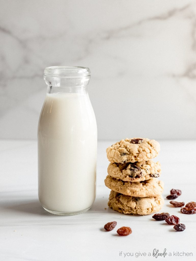 stack of four oatmeal raisin cookies next to glass bottle of milk