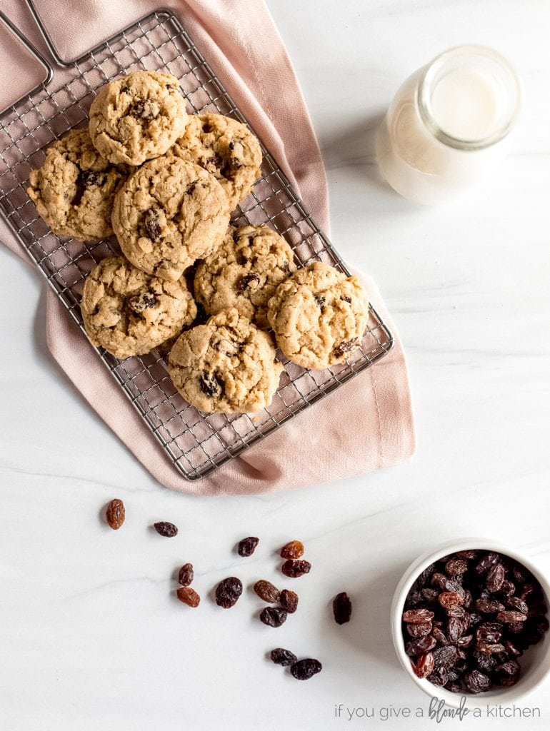 oatmeal raisin cookies on wire rack, small bowl of raisins
