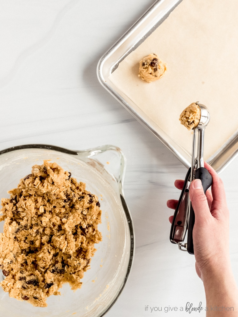 hand spooning oatmeal raisin cookie dough onto parchment lined baking sheet