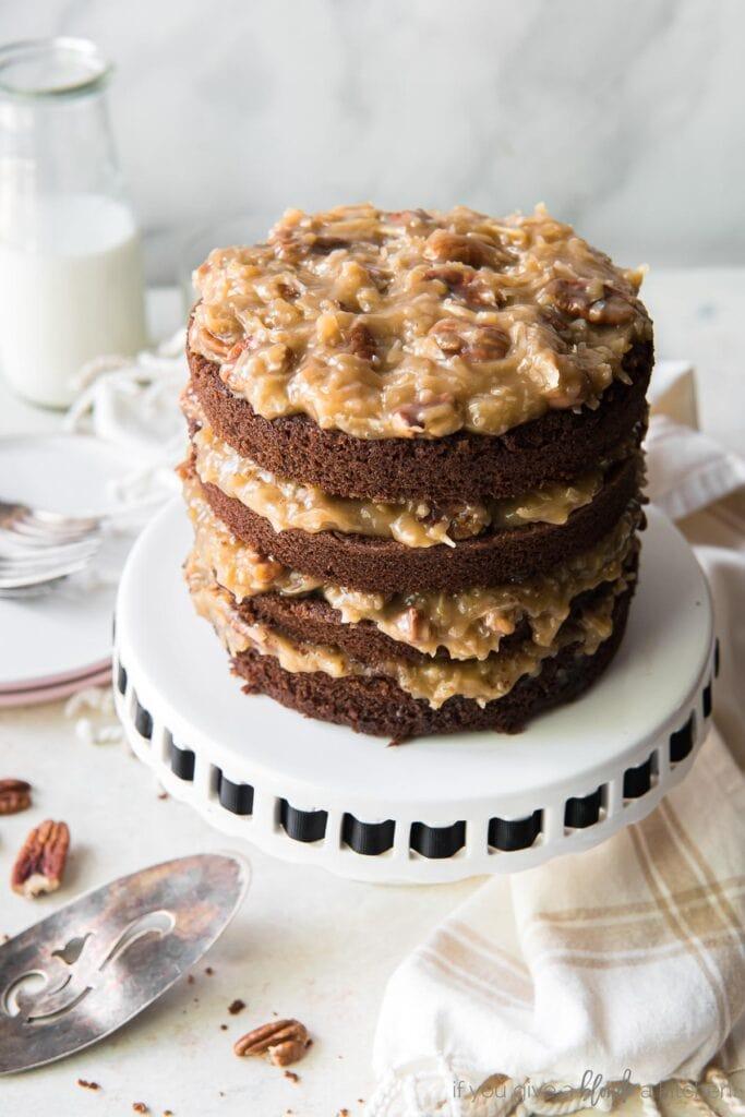 layered german chocolate cake on white cake stand