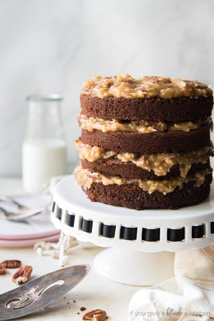 layered german chocolate cake on a white cake stand