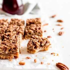 maple pecan bars with bite showing shortbread crust and chopped nuts