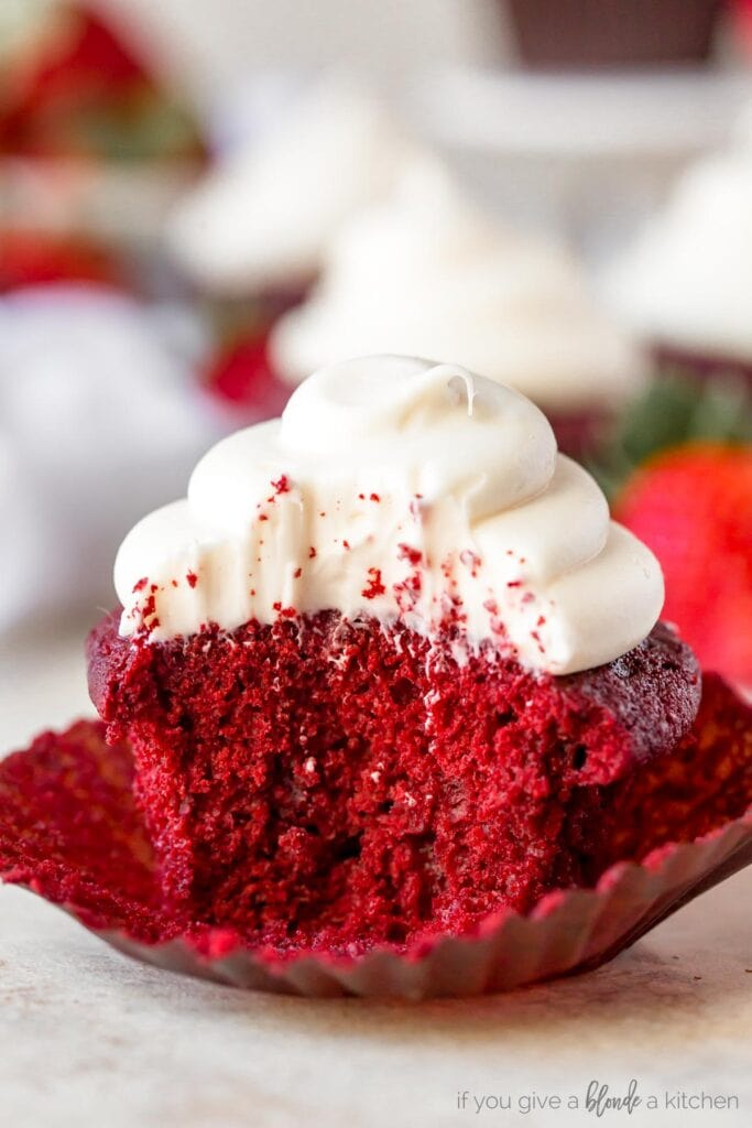 red velvet cupcake with cream cheese frosting and a bite taken