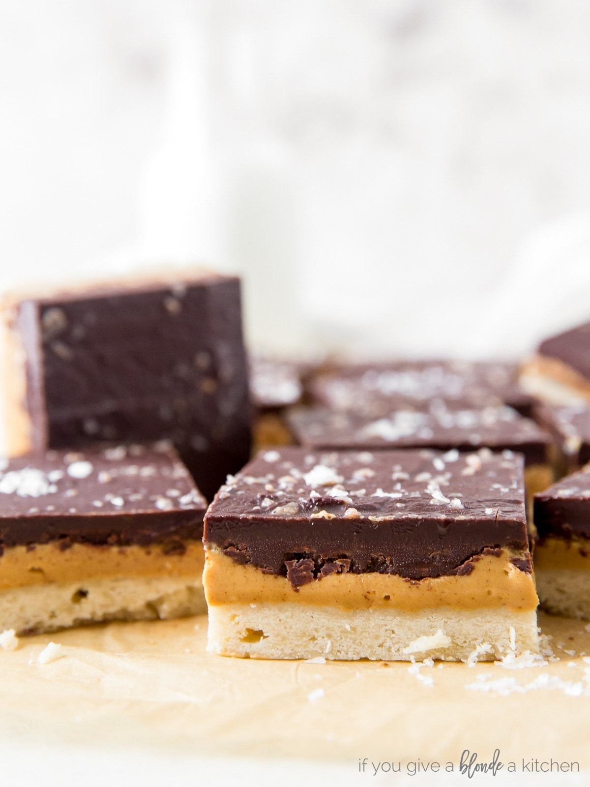 side of peanut butter chocolate bar showing layers of shortbread crust, peanut butter filling and chocolate topping