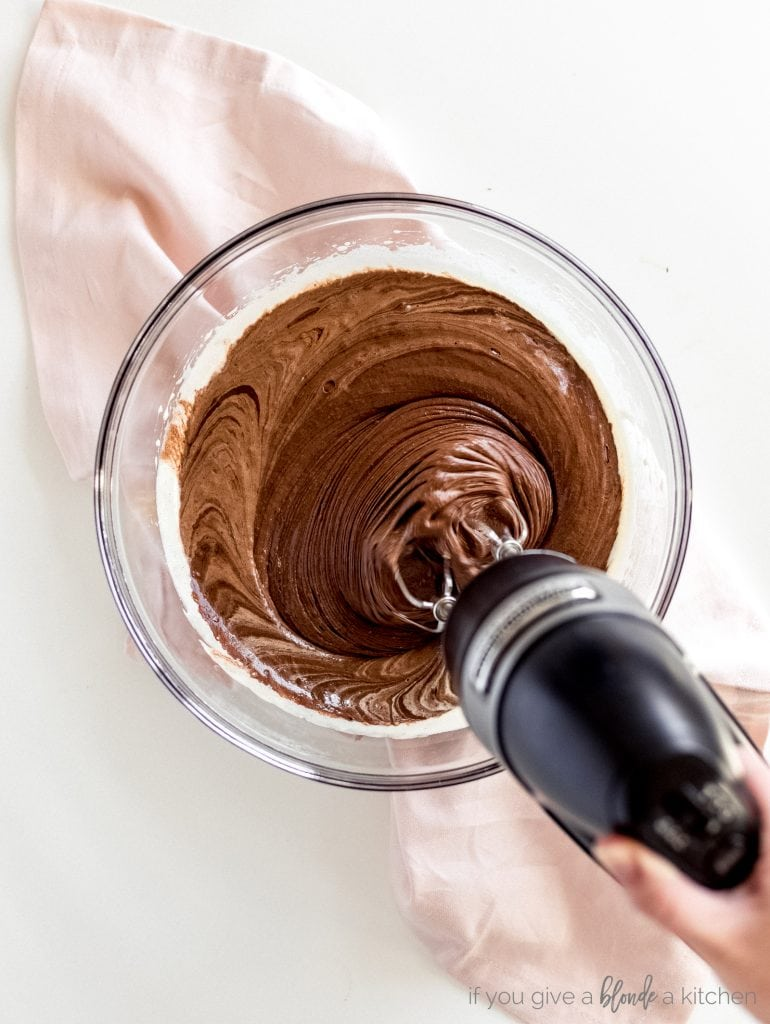 hand mixer combining brownie ingredients