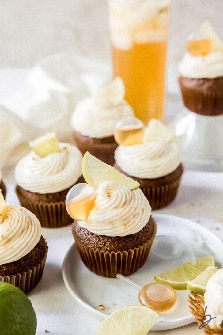 dark and stormy cupcake on a small white plate with lime slices and pipettes
