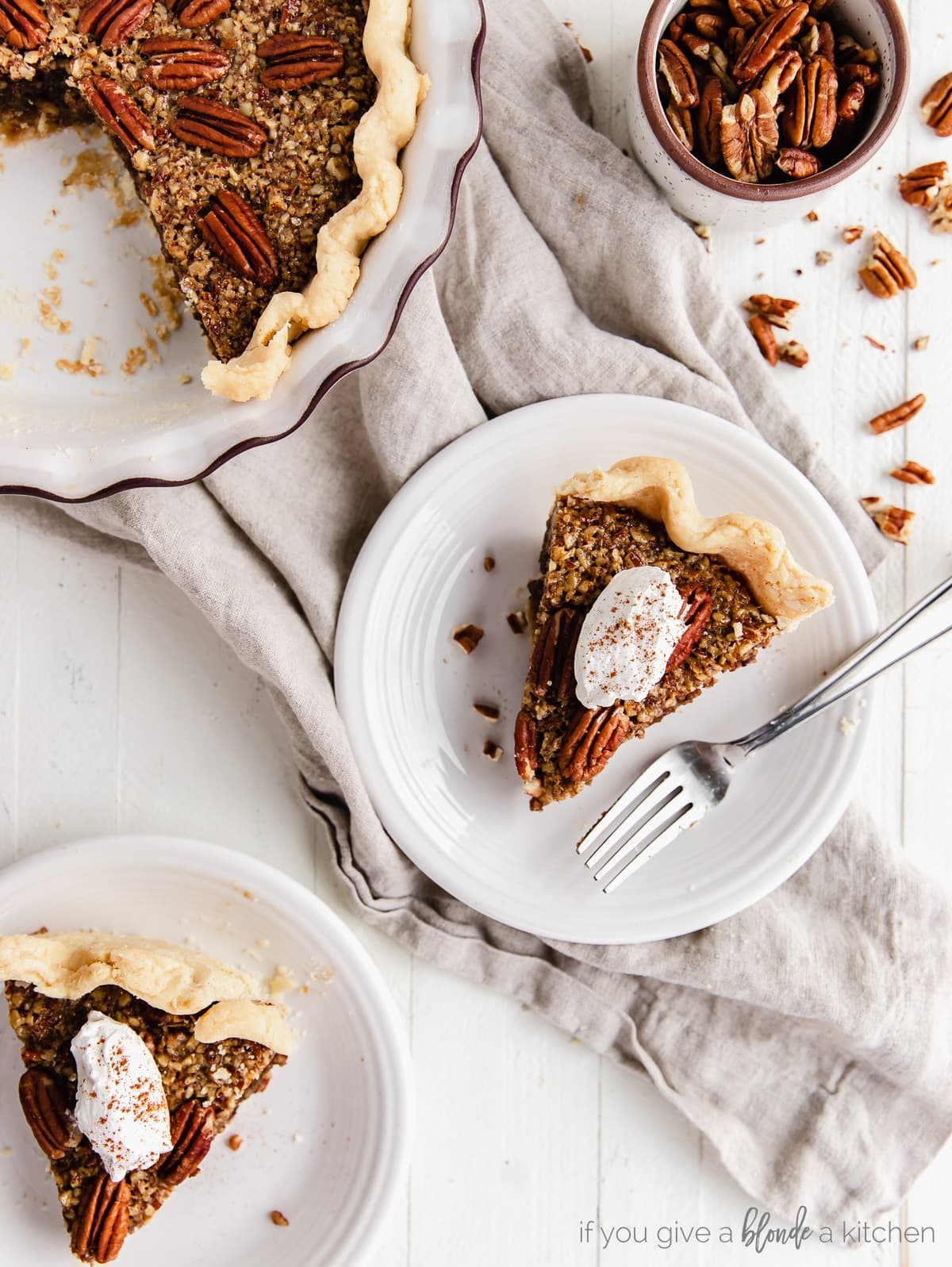 two slices of pecan pie with dollop of whipped cream on round white plates