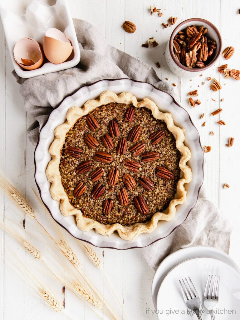 pecan pie in a ceramic pie dish with pecan halves on top arranged to radiate out