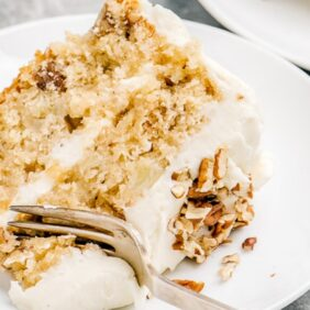 slice of double layer hummingbird cake on plate with fork