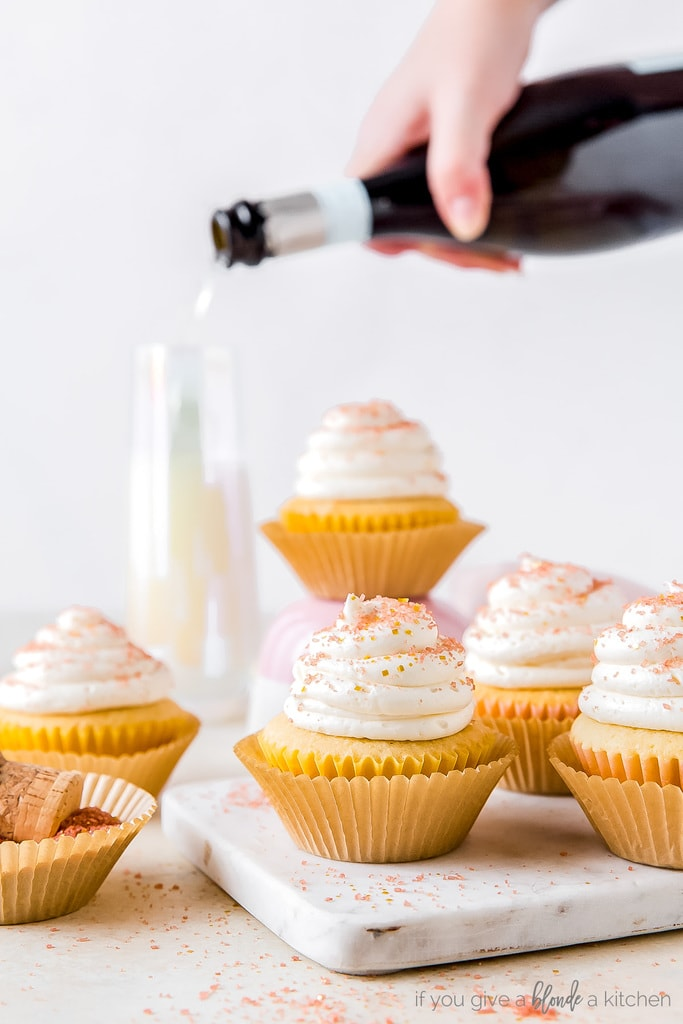champagne cupcakes on marble slab; hand pouring bottle of champagne into glass behind cupcakes