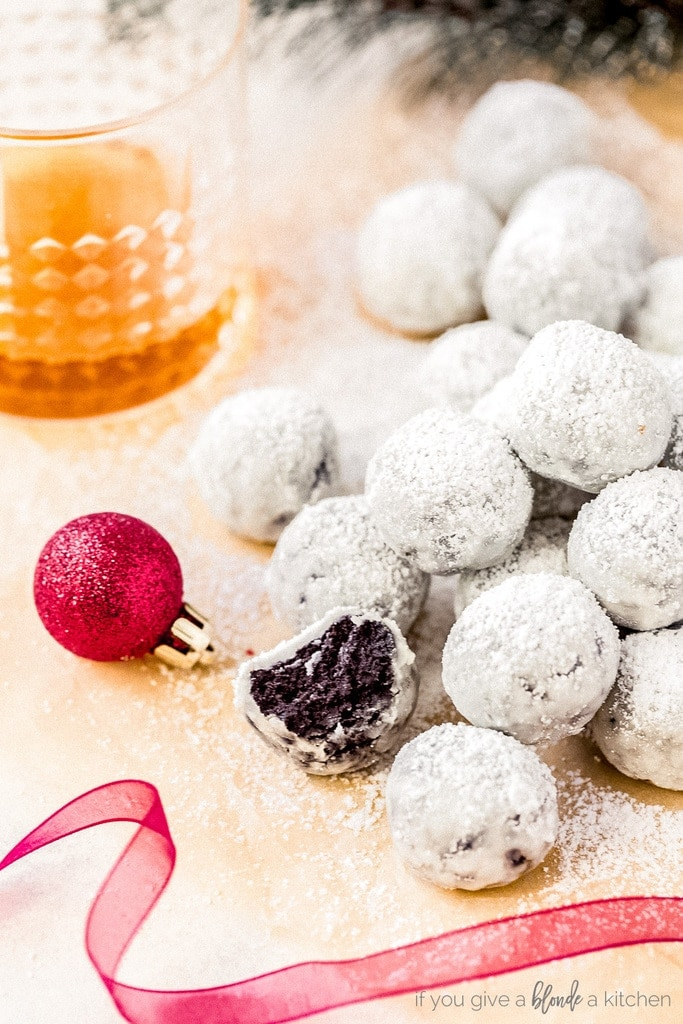 powdered sugar covered rum balls; one rum ball with bite next to small red christmas ornament