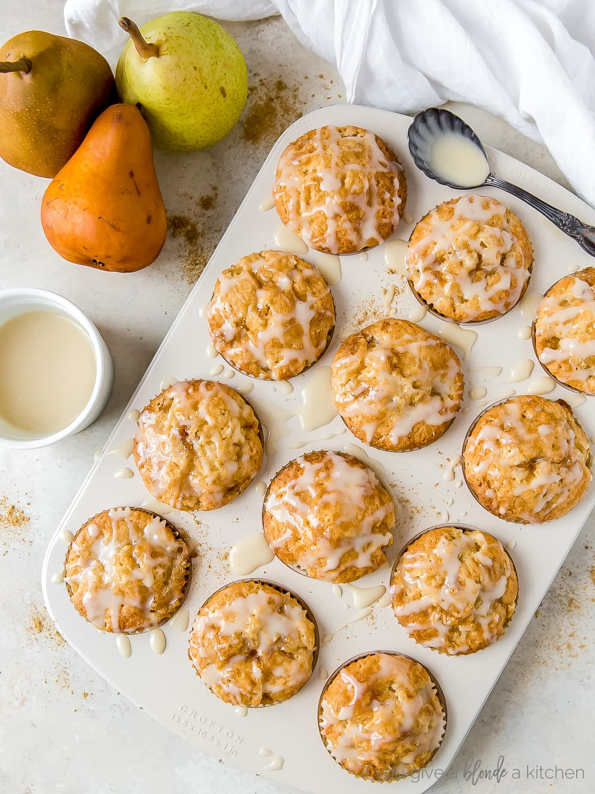 glazed ginger pear muffins in a muffin tin; pears next to muffin tin