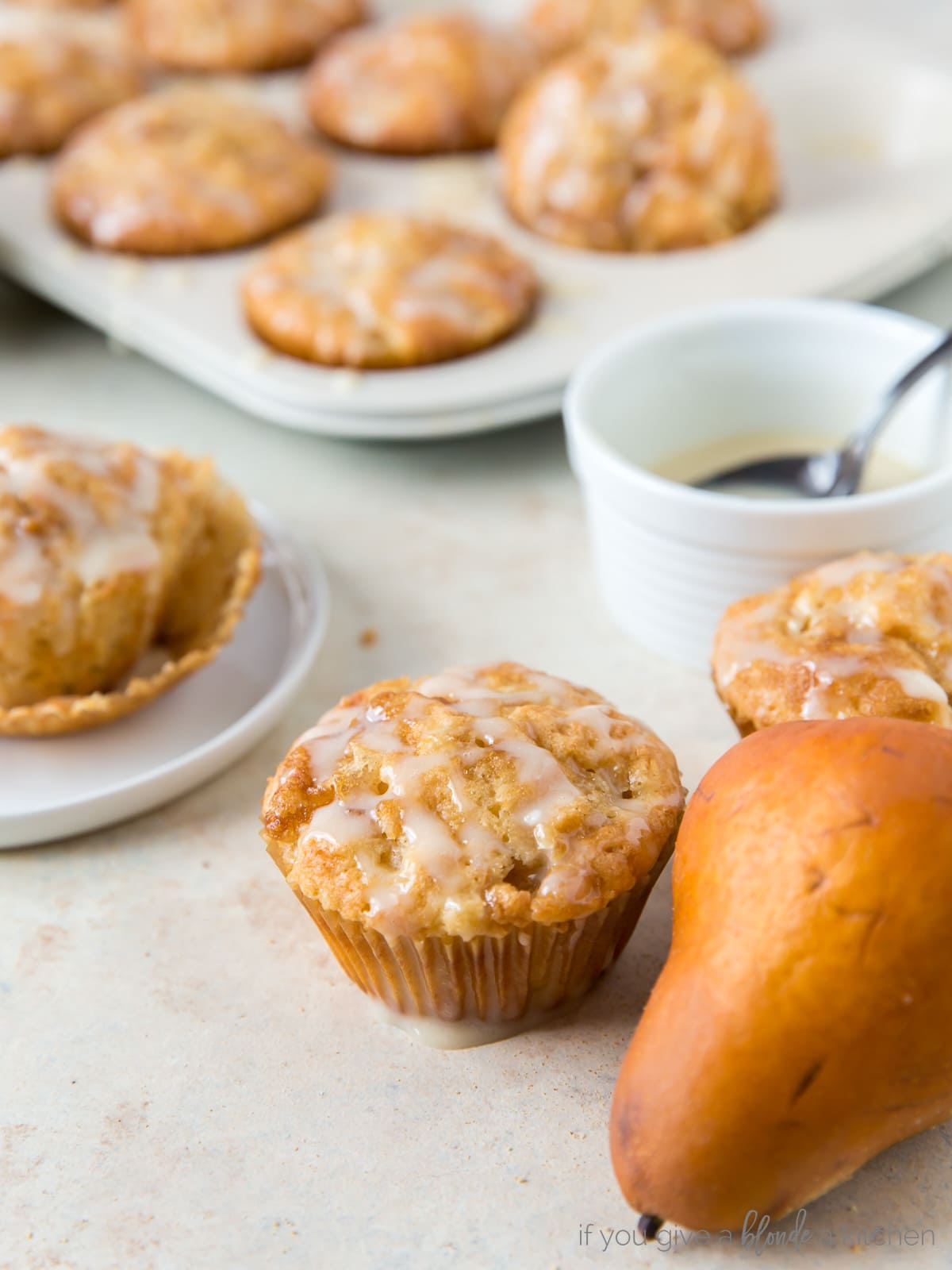 ginger pear muffin next to brown pear and bowl of honey glaze