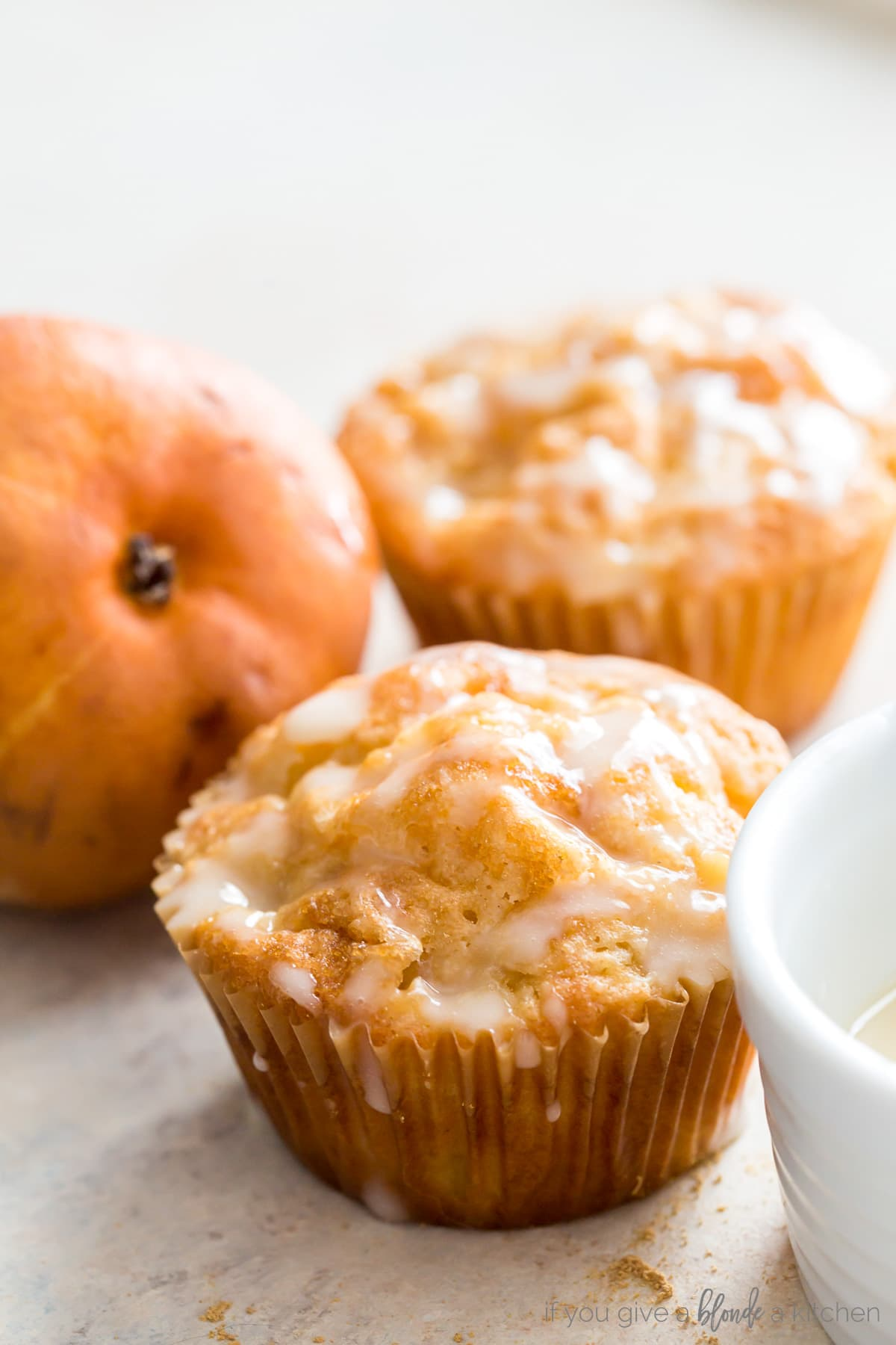 two ginger pear muffins with glaze next to brown pear