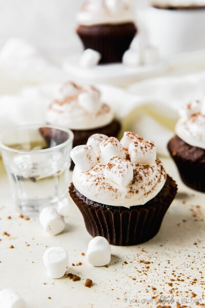 two hot cocoa cupcakes topped with marshmallow frosting and cocoa, mini marshmallows next to cupcake