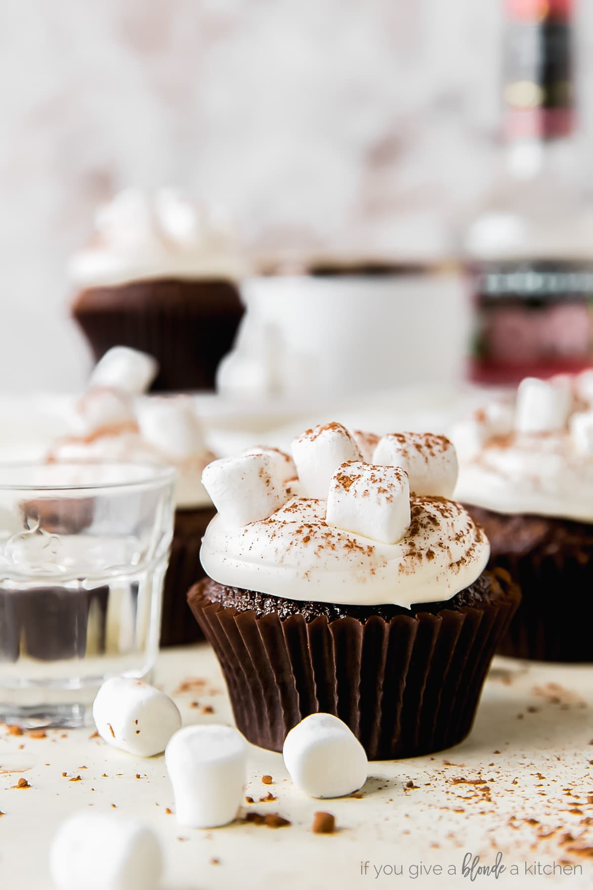 hot cocoa cupcake topped with marshmallow frosting, next to shot glass of peppermint schnapps