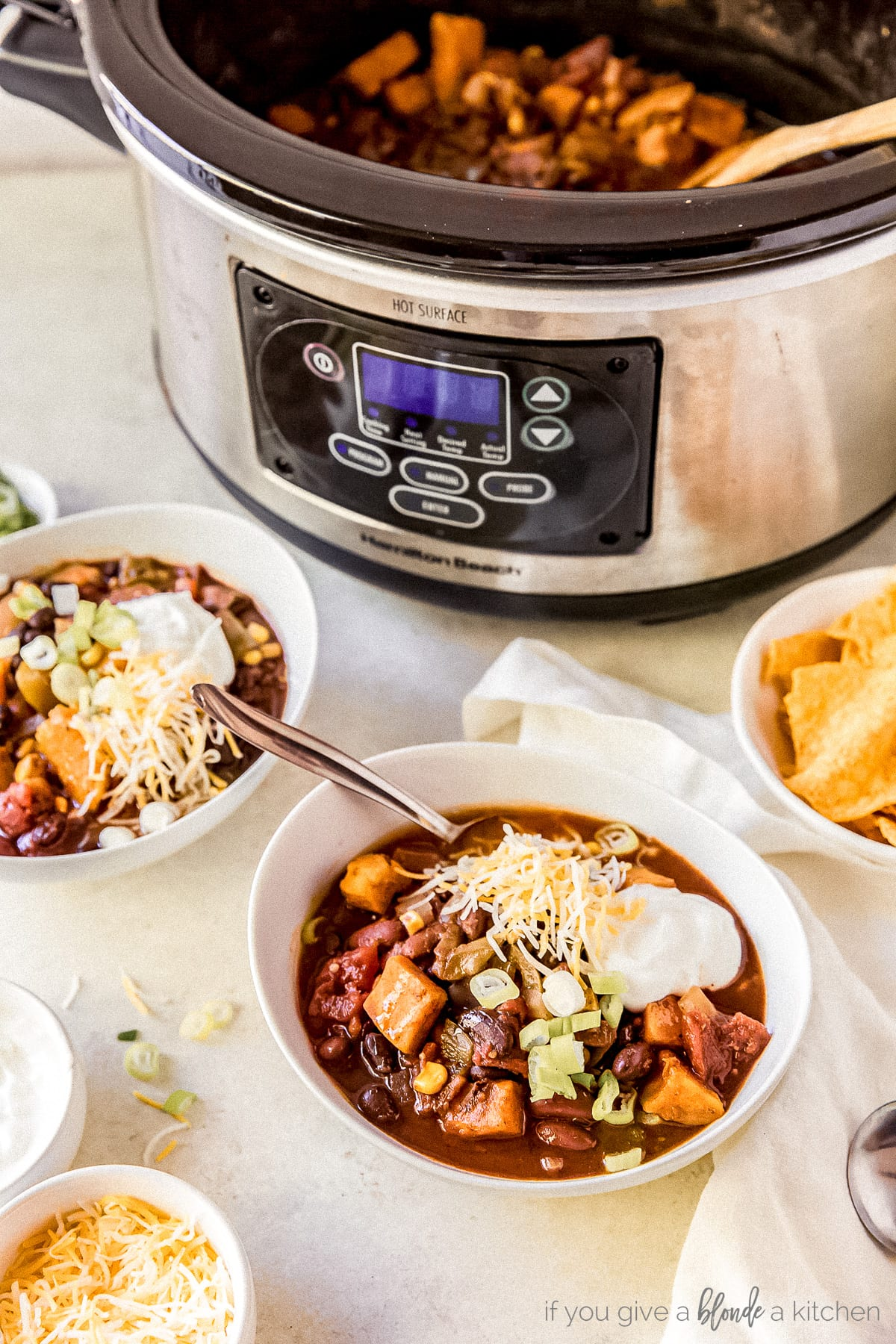 two bowls of sweet potato chili in front of stainless steel slow cooker full of chili