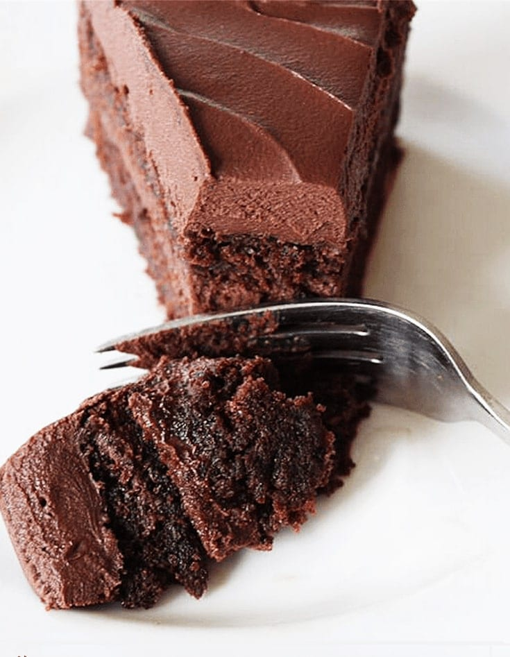 decadent chocolate cake recipe fork taking a bite from two layer cake with chocolate frosting