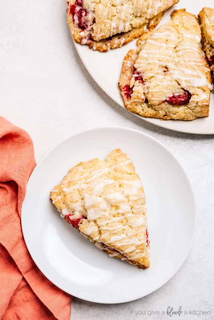 lemon raspberry scone on round white plate and coral cloth