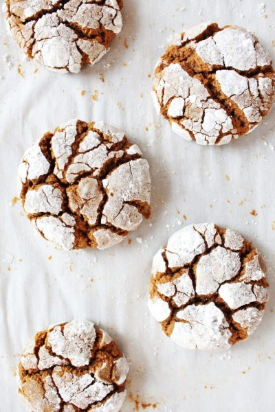 gingerbread crinkle cookies coated in powdered sugar on parchment paper