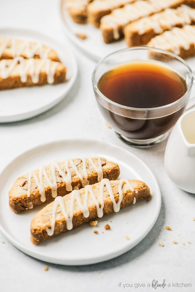 two almond biscotti with vanilla glaze on round white plate; clear mug of coffee next to plate