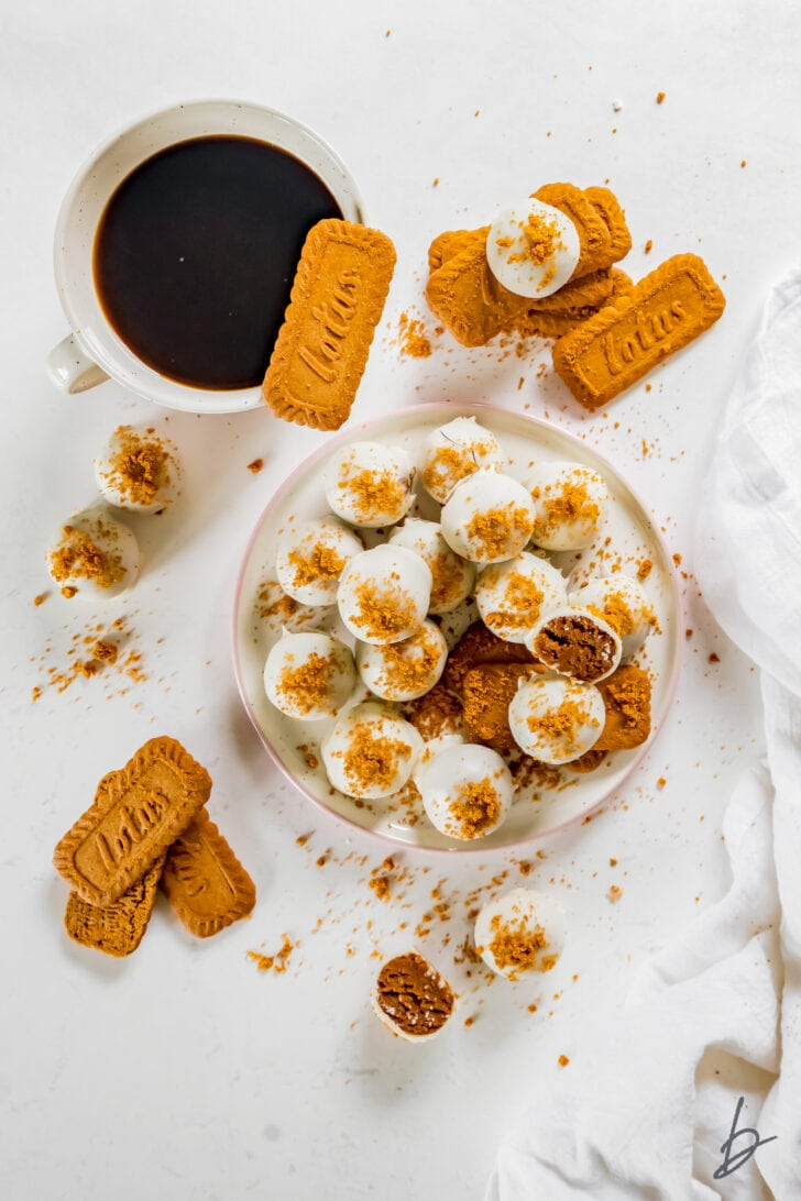 plate of white-chocolate covered biscoff truffles with cookie crumbs next to more biscoff cookies and mug of coffee