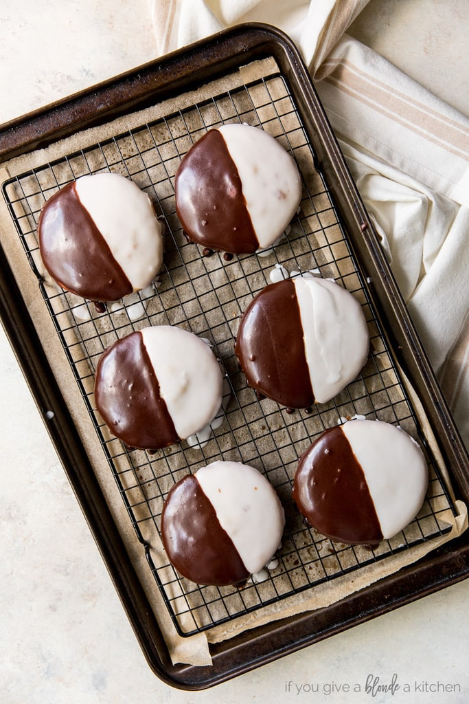 six black and white cookies on wire rack on parchment paper