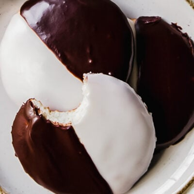 three black and white cookies on a white round plate; top cookie with a bite