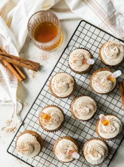 buttered rum cupcakes topped with frosting, cinnamon and rum on wire cooling rack